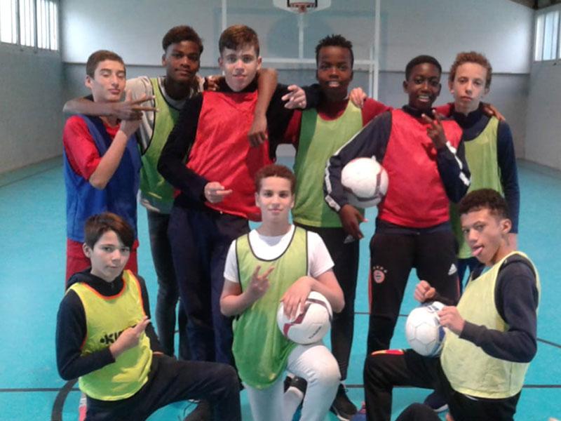 Groupe d'enfants et adolescents jouant au football en intérieur en colonie de vacances