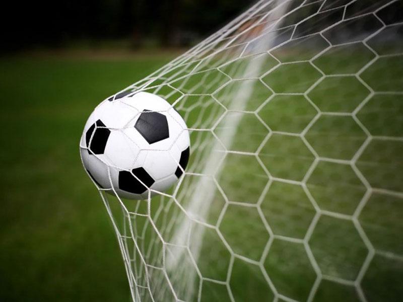 Balle de football dans le filet du but de football en colonie de vacances