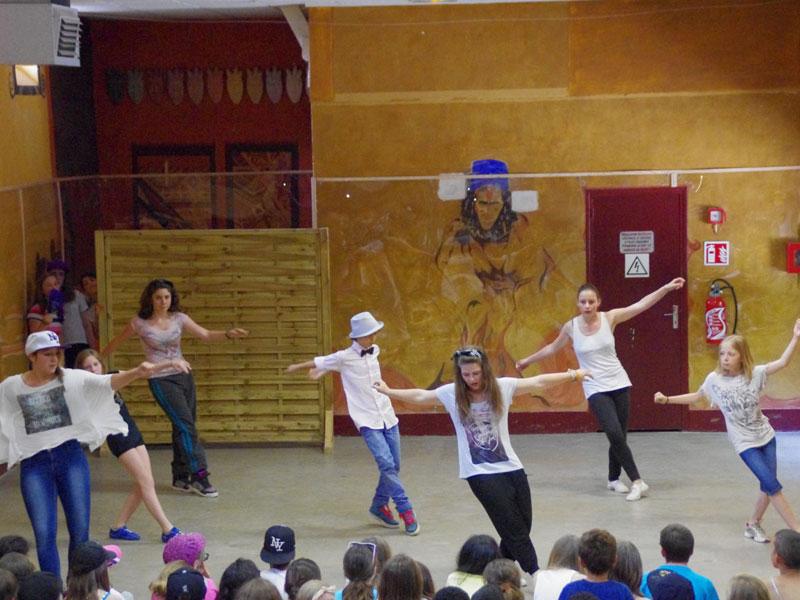 Groupe d'ados dansant devant d'autres enfants en colonie de vacances artistique