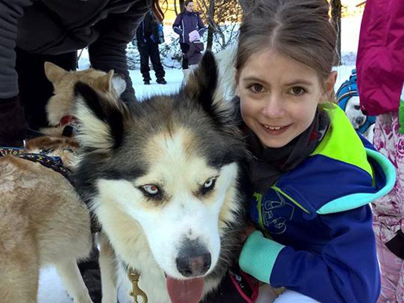 Enfant avec les chiens de traîneaux en colonie de vacances