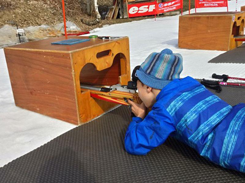 Enfant pratiquant le tir laser en colonie de vacances à la neige