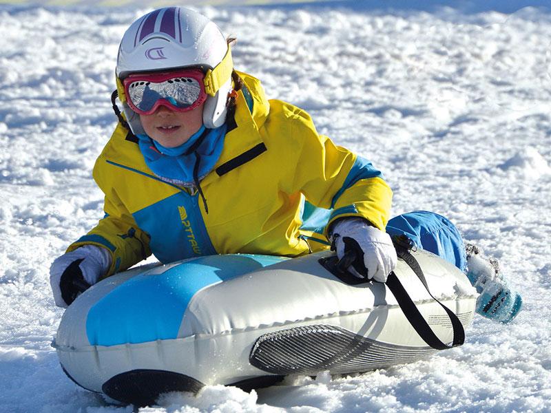 Enfant pratiquant la luge airboard en colonie de vacances