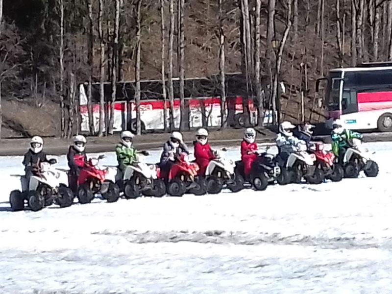 Groupe d'enfants en colonie de vacances faisant du quad dans la neige