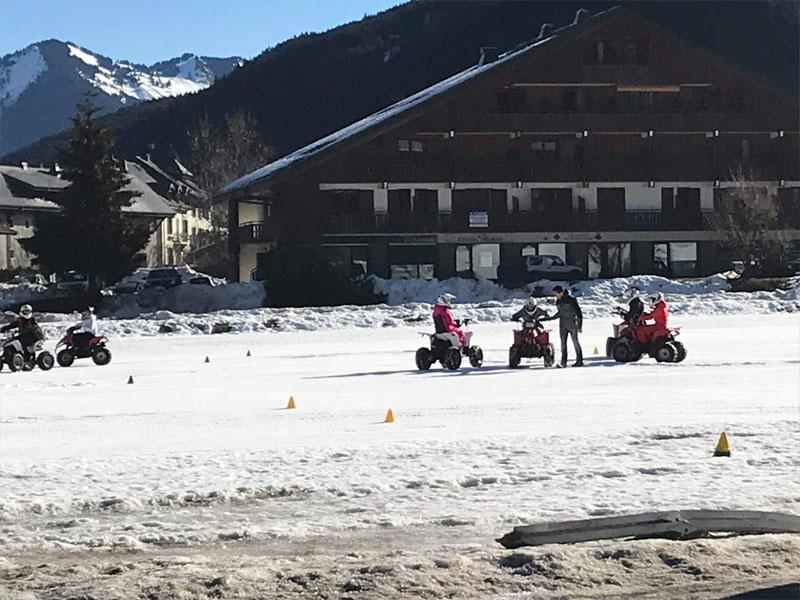 Ado conduisant un quad dans la neige en colonie de vacances