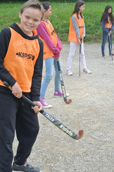 Enfants apprenant à jouer au hockey en colonie de vacances