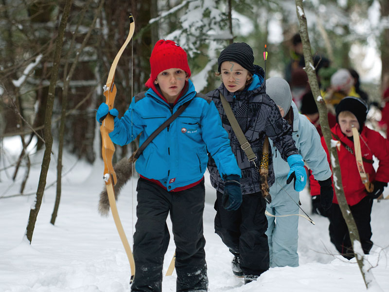 Enfants pratiquant le tir à l'arc des neiges en colonie de vacances