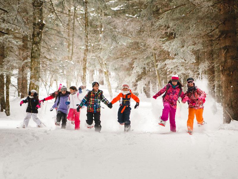 Groupe d'enfants en randonnée à raquettes en colo
