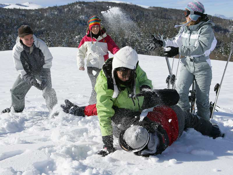 Groupe d'ados qui jouent dans la neige en colonie