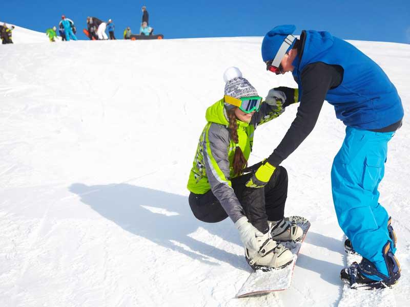 Ado qui apprend le snowboard avec un moniteur de ski