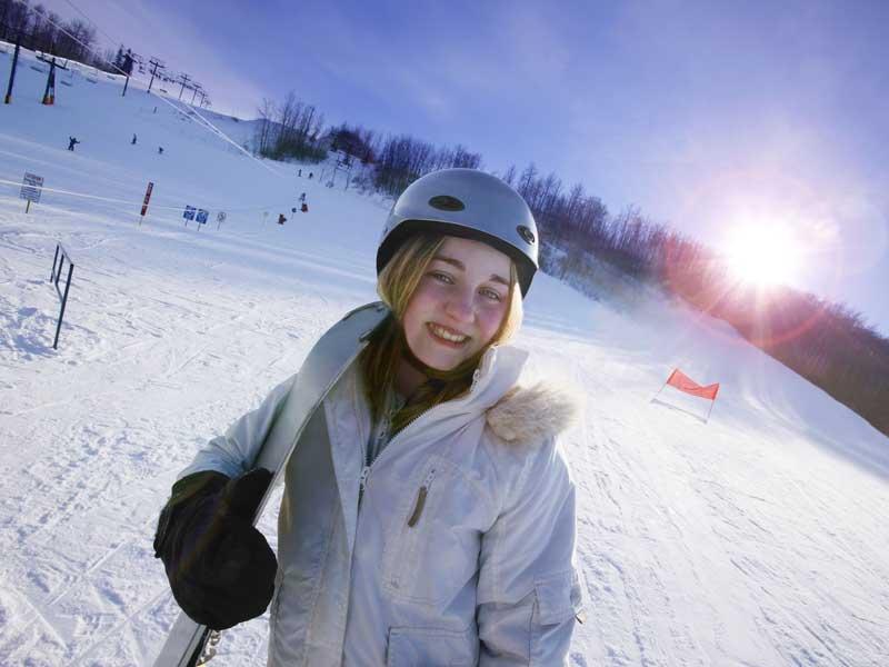 Jeune fille qui sourit avec son surf en colonie de vacances à la neige