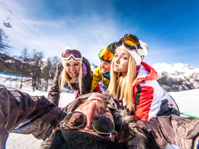 Quatre ados qui jouent dans la neige en vacances d'hiver