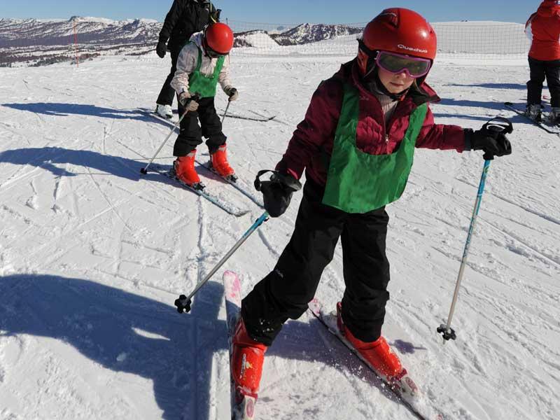 Enfant pratiquant le ski en colonie de vacances d'hiver