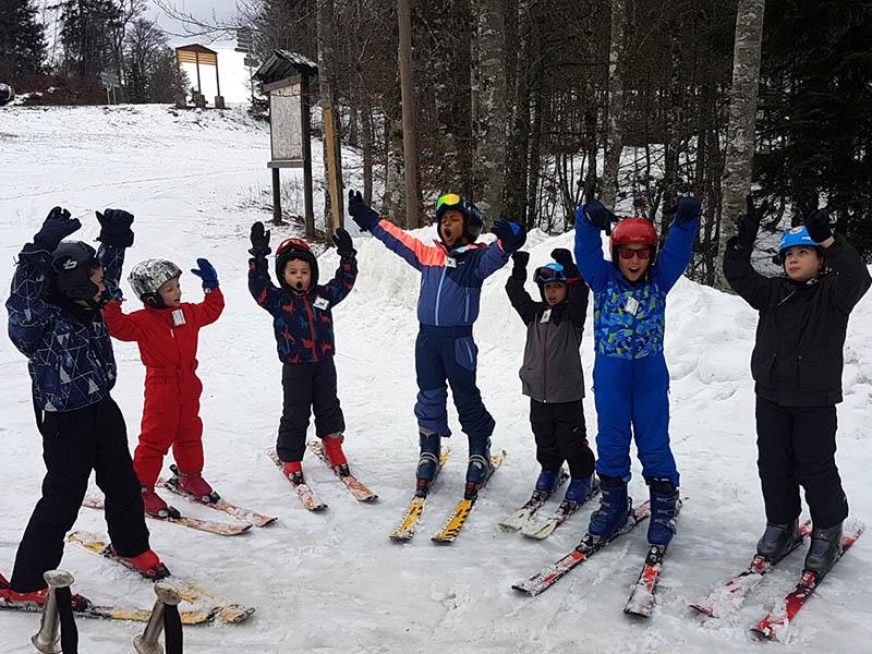Groupe d'enfants dans la neige en colonie de vacances de février