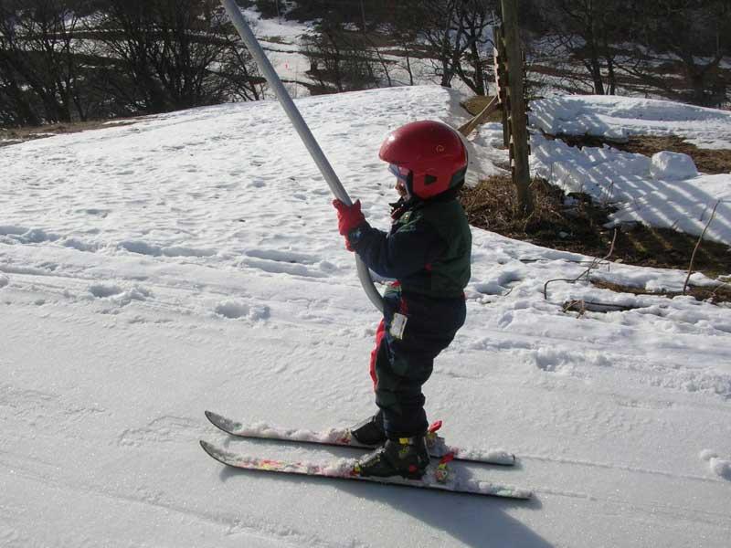 Enfant sur le tire fesse en colonie de vacances au ski