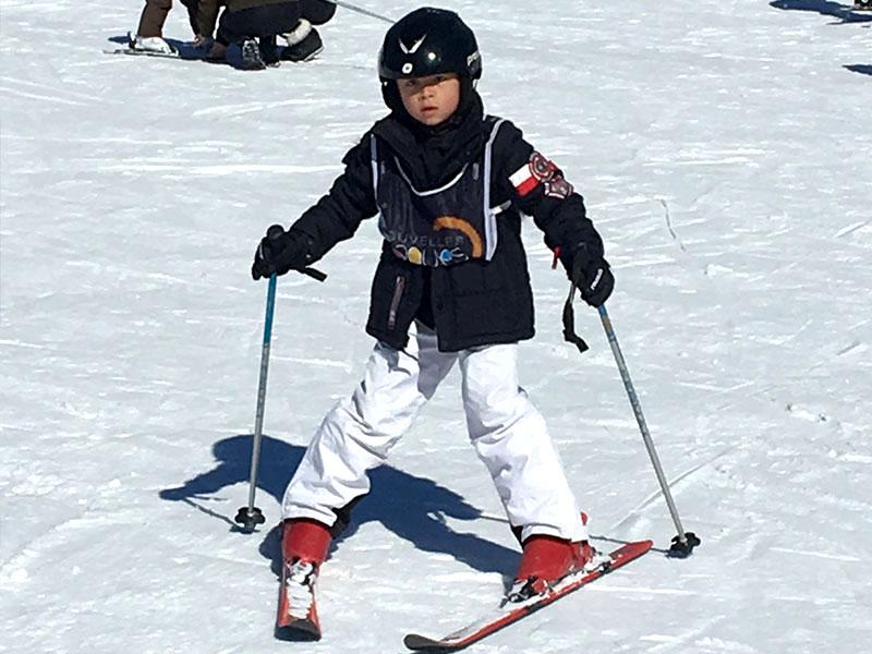 Jeune enfant de 7 ans apprenant à skier en colo cet hiver