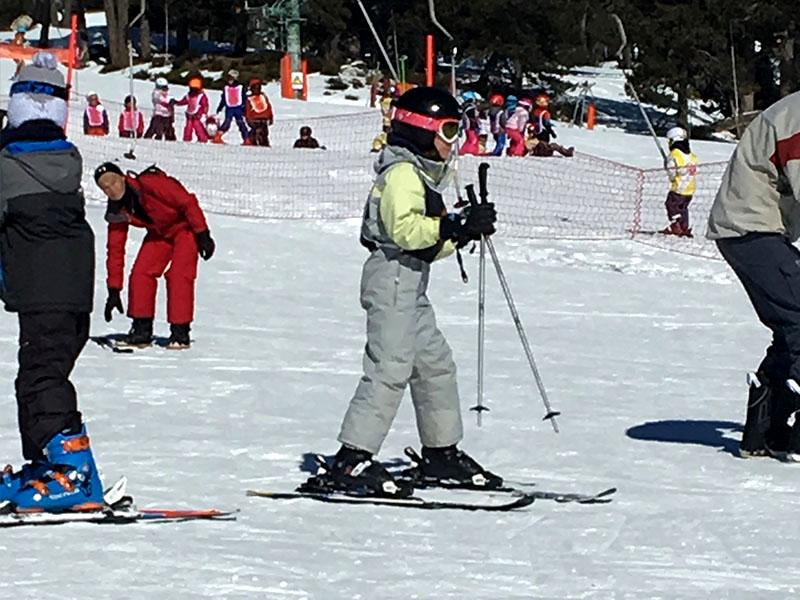 Fillette apprenant à skier en colonie de vacances d'hiver