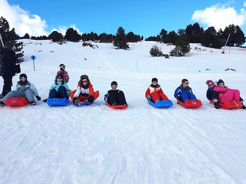 Groupe d'enfants en luge cet hiver en colonie de vacances