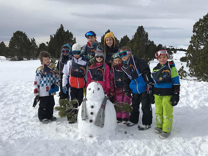 Groupe d'enfants de 8 ans faisant des bonhommes de neige en colo