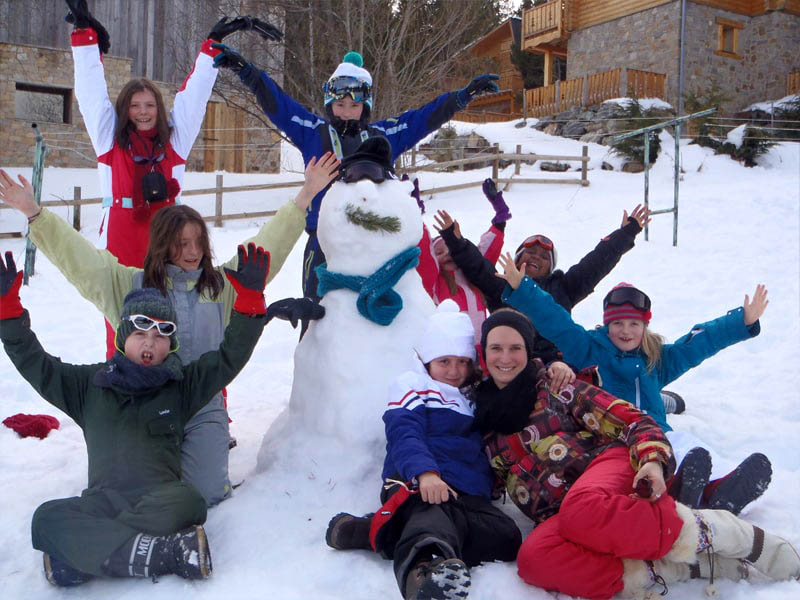 Groupe d'enfants heureux devant leur bonhomme de neige en colonie de vacances