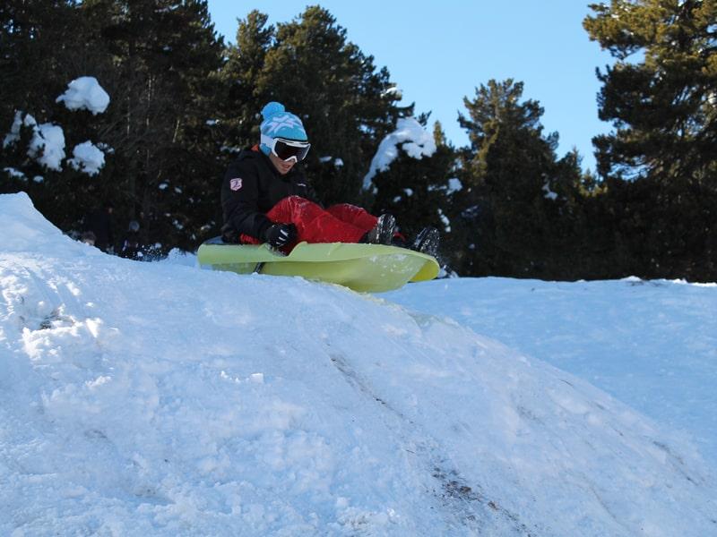 Enfant de 8 ans faisant des glissades à luge dans la neige en colonie de vacances