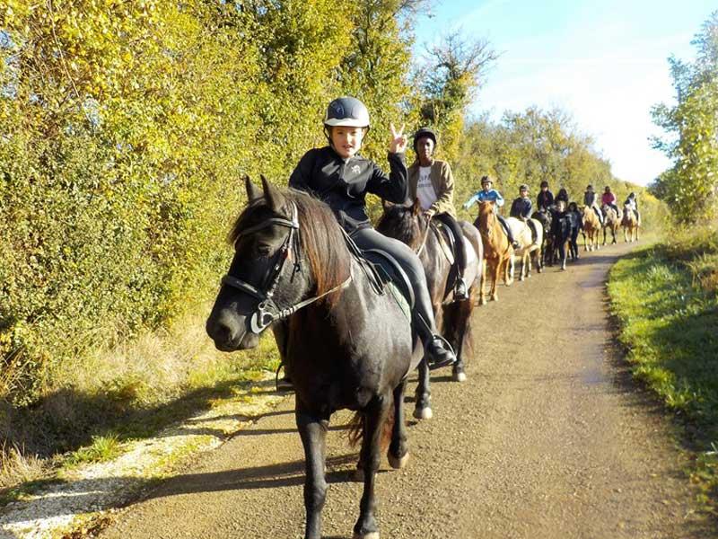 Enfants en colonie de vacances en balade à poney