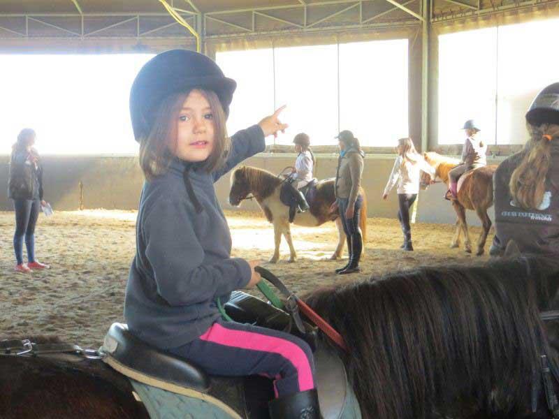 Enfant à poney en colonie de vacances