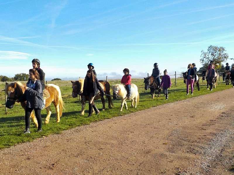 Groupe d'enfants en balade à cheval en colo