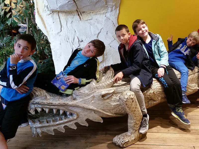 Enfants sur un crocodile factice en colonie de vacances cet hiver