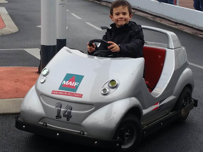 Enfant dans une petite voiture en colonie de vacances d'hiver