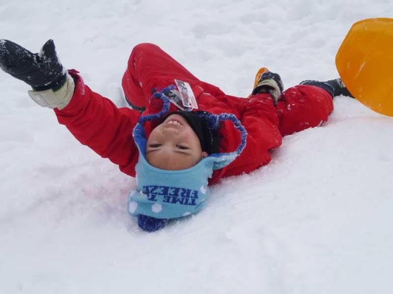 Enfant s'amusant dans la neige en colonie de vacances