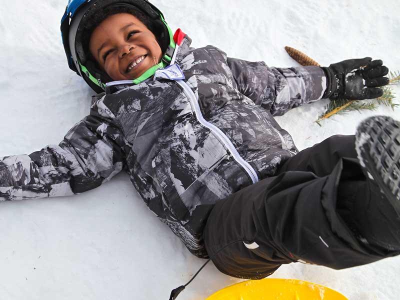 Enfant qui s'amuse dans la neige en luge en colonie de vacances