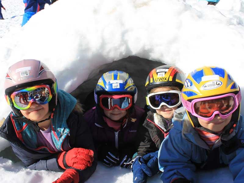 Groupe d'enfants dans un igloo en colonie de vacances d'hiver