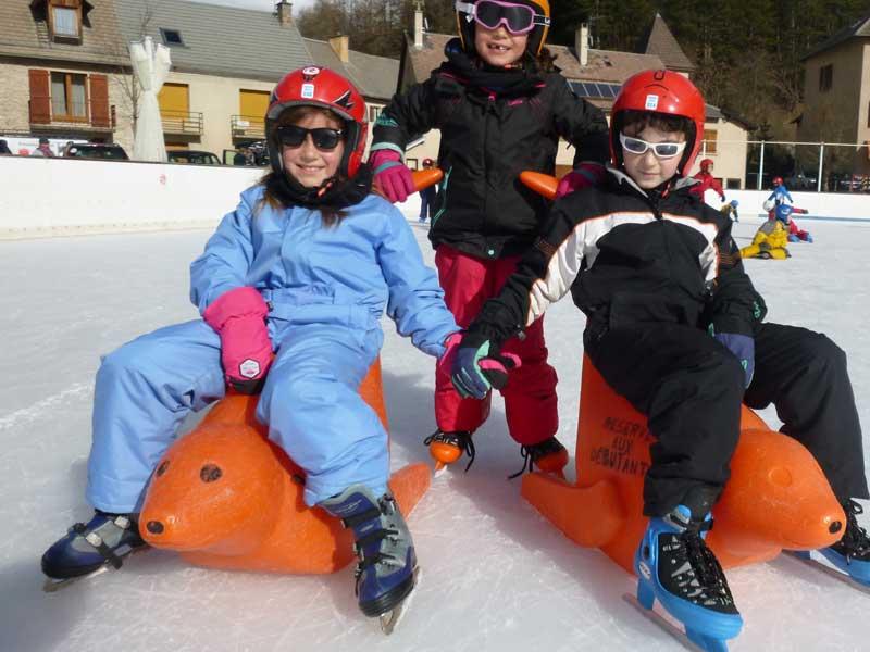 Trois enfants s'amusant sur la patinoire cet hiver
