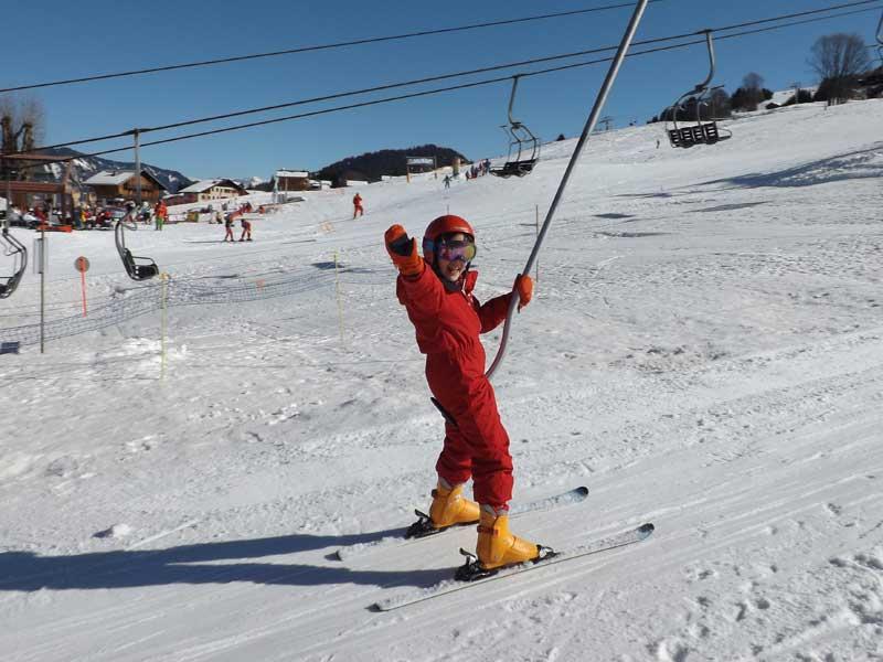 Enfant sur un tire fesse sur les pistes de ski de colonie de vacances cet hiver