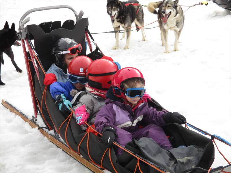 Enfants sur un traineau en colonie de vacances cet hiver