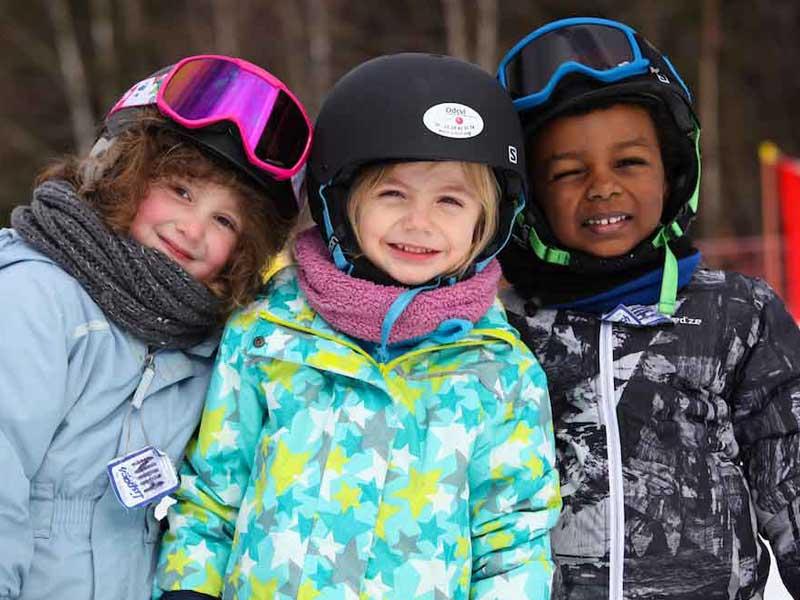 Portrait de trois enfants en colonie de vacances cet hiver sur les pistes de ski