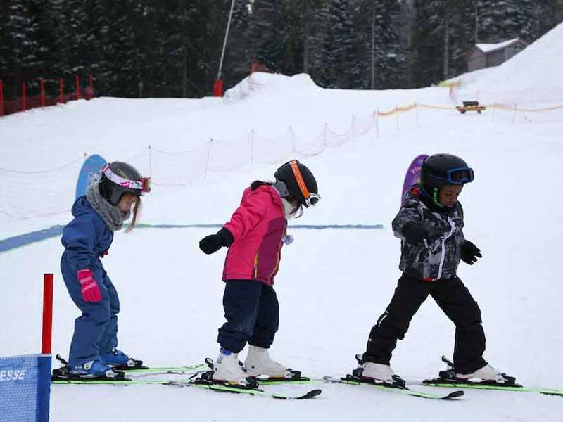 trois enfants apprenant à faire du ski en colo cet hiver