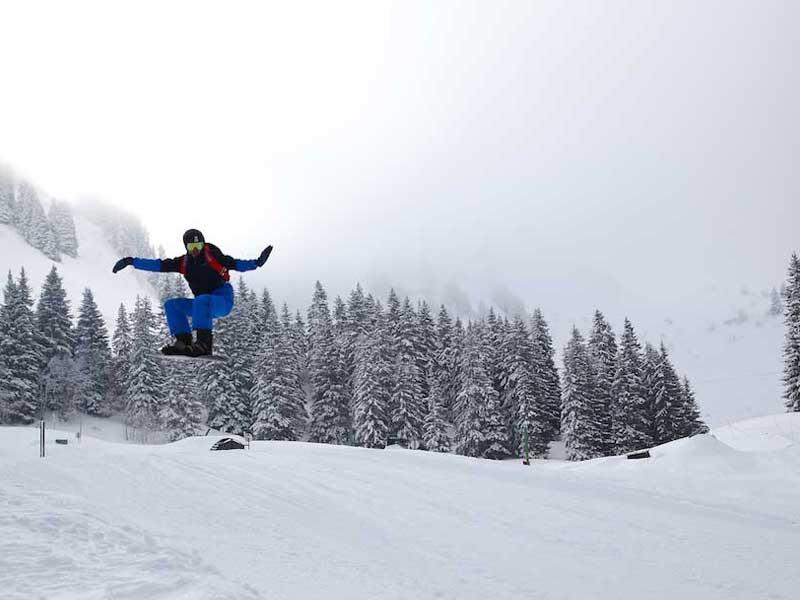 Ados pratiquant le saut en snowboard en colonie de vacances