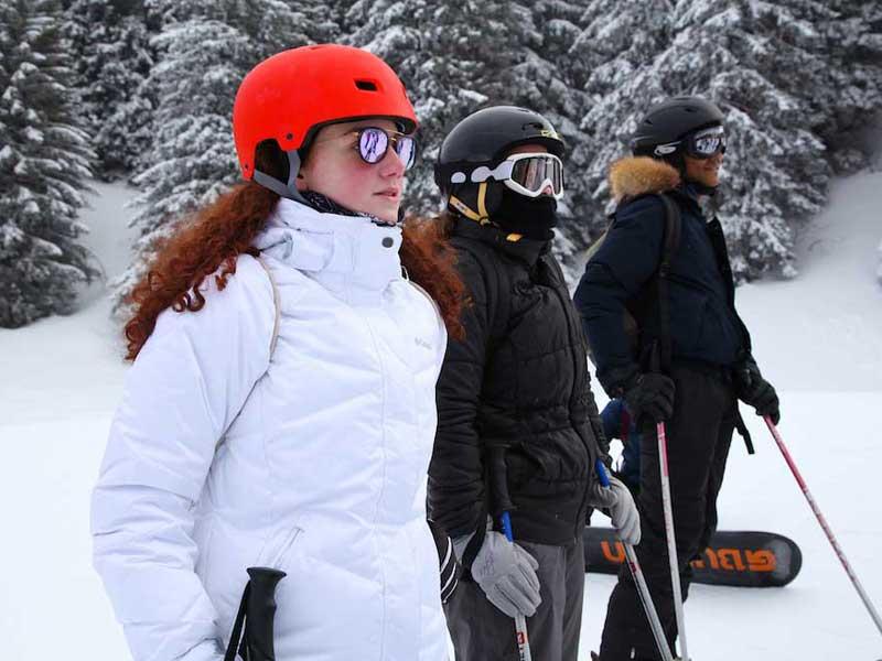 Ados sur les pistes de snowboard et ski en colonie de vacances à la montagne