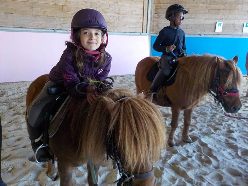 Enfants montant à poney en colonie de vacances d'hiver