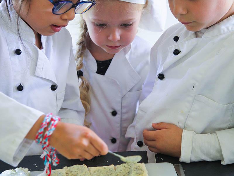 Enfants en train de cuisiner en colonie de vacances d'hiver
