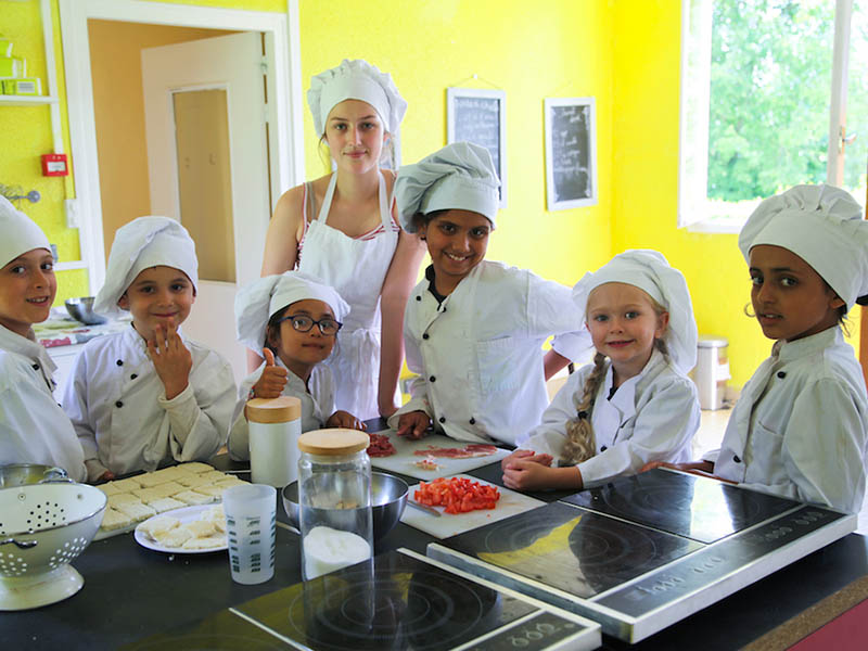 Groupe d'enfants en train de cuisiner en colo