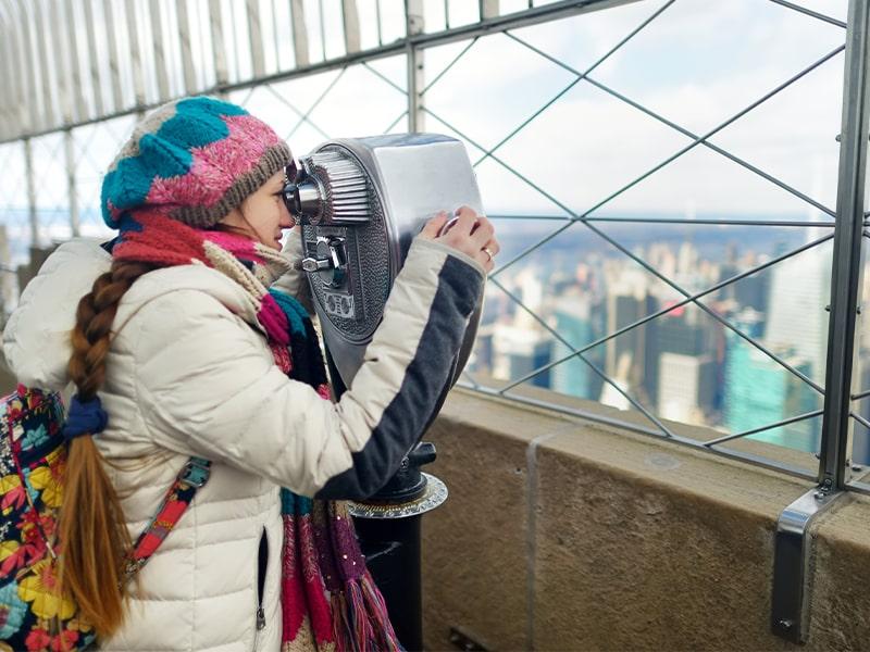Jeune fille qui observe la ville de New York dans une jumelle lors d'une colonie de vacances à New York