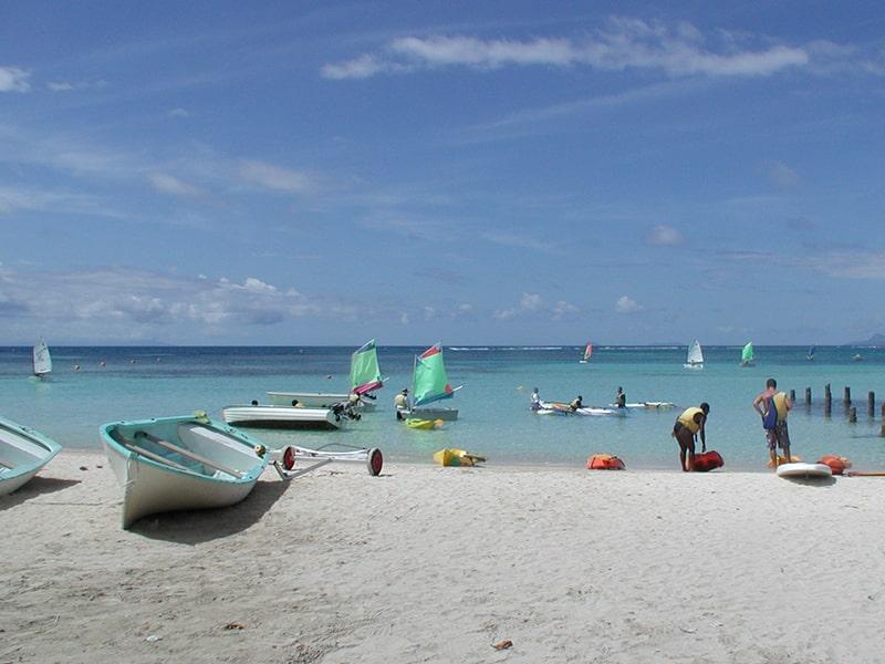 Vue sur le bord de plage avec des bateaux et un grand soleil bleu lors d'une colo de vacances en Guadeloupe durant l'hiver