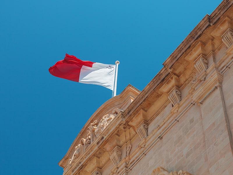 Vue sur le drapeau de Malte accroché à un ancien bâtiment et avec un grand ciel bleu