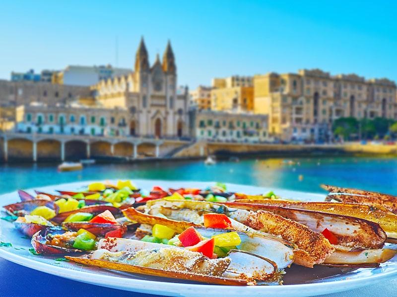 Plat typique de Malte avec vue sur les monuments célèbre et sur la mer Méditerranée lors d'une colonie de vacances à Malte