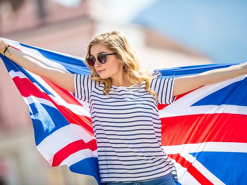 Jeune fille en colonie de vacances à Londres avec un drapeau anglais