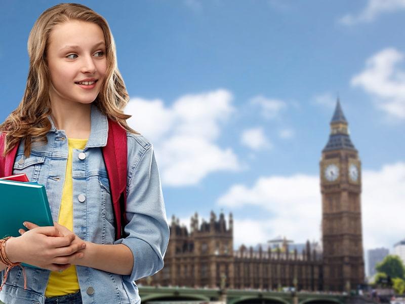 Enfant avec des cahiers devant Big Ben lors d'une colonie de vacances à Londres