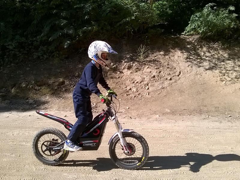 jeune enfant apprenant à conduire une moto électrique en colo
