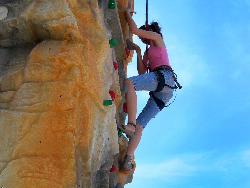 Jeune fille pratiquant l'escalade en colonie de vacances